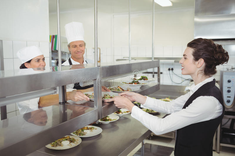 Chef handing food dish to waitress at order station. In the commercial kitchen stock image