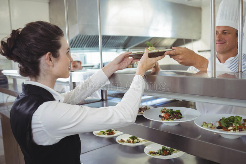 Chef handing food dish to waitress at order station. In the commercial kitchen royalty free stock photos