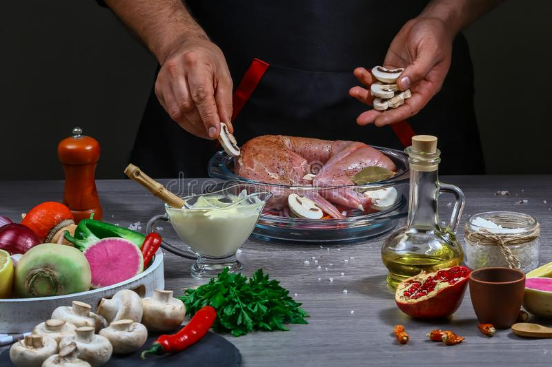 Chef hands cooking roasted rabbit with sour cream sauce with vegetables. A festive meal. gourmet food royalty free stock images