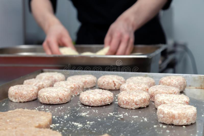 Chef hands creating, forming, breading chicken cutlet with knife on professional restaurant kitchen. Concept fast food business,. Chef hands creating, forming stock image