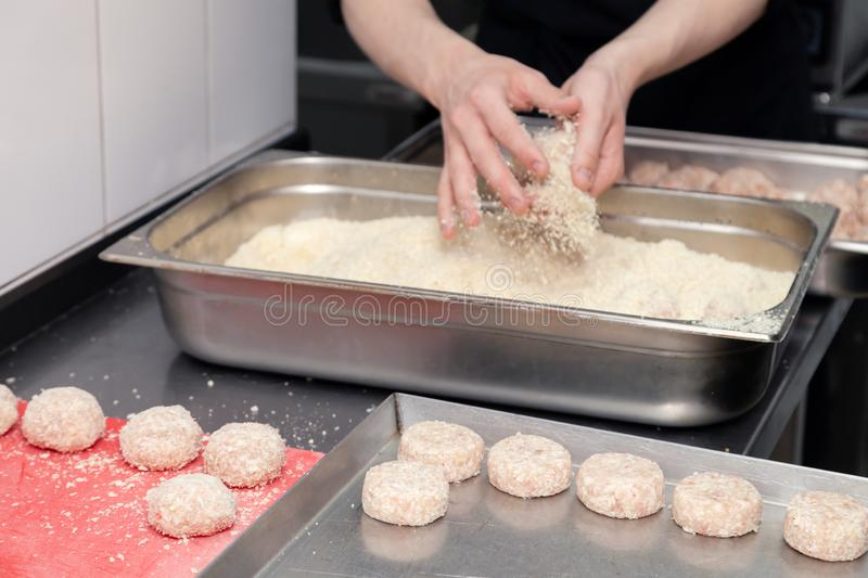 Chef hands creating, forming, breading chicken cutlet with knife on professional restaurant kitchen. Concept fast food business,. Chef hands creating, forming stock images