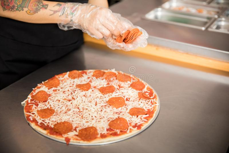 Chef hands with gloves holding pepperoni slices for pizza toppings stock image