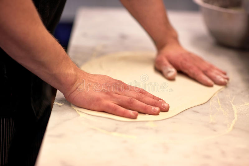 Chef hands preparing dough on table at kitchen royalty free stock photography