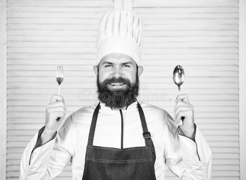 Chef happy smiling face hold spoon and fork. Man handsome with beard holds kitchenware on white background. Cooking royalty free stock images