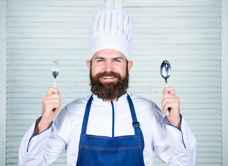 Chef happy smiling face hold spoon and fork. Man handsome with beard holds kitchenware on white background. Cooking stock images
