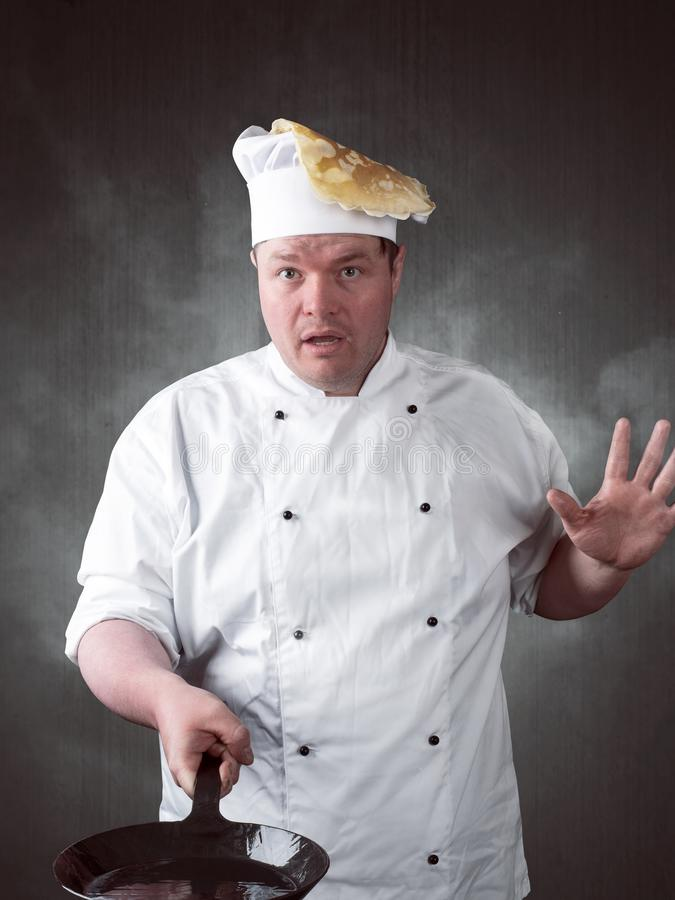Chef turns fresh pancakes in the pan stock image