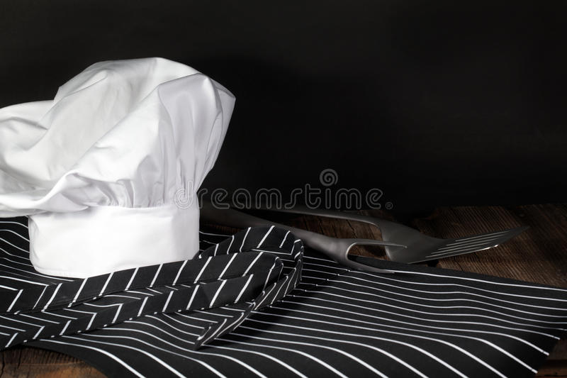 Chef Hat and Apron. A white chef hat, a black and white striped chefs apron, a spatula and a fork on wood surface and black background stock photos