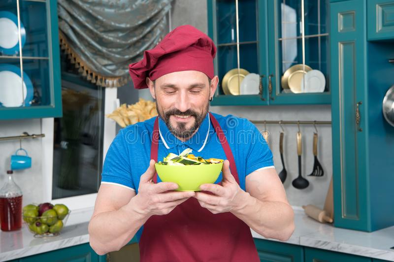 Chef in hat holds yellow plate with salad in hands and sniff. Smiling bearded man in apron and hat loves salad. royalty free stock photos