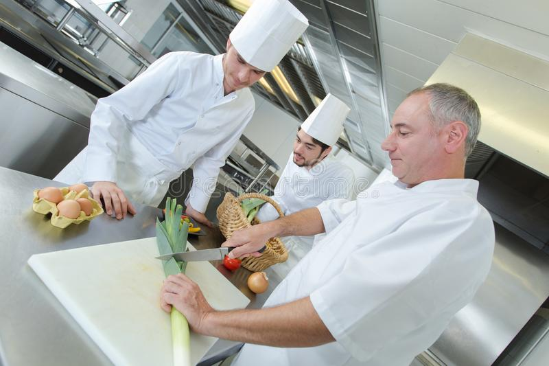 Chef and helpers in kitchen royalty free stock images