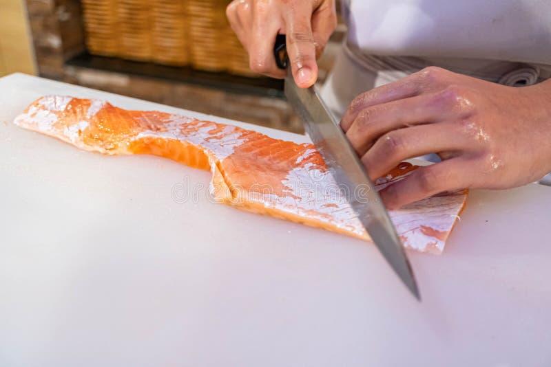 Chef in het bereiden en snijden van verse zalm in Japans restaurant stock afbeeldingen