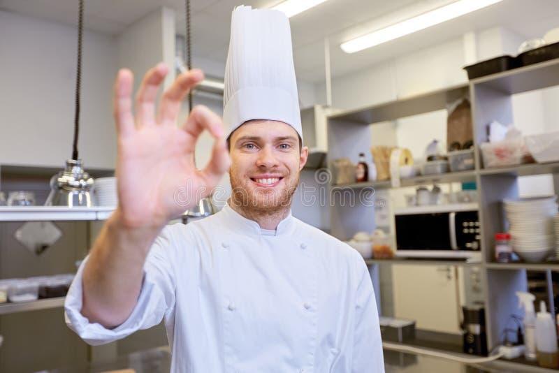 Chef heureux à la cuisine de restaurant montrant le signe correct photographie stock