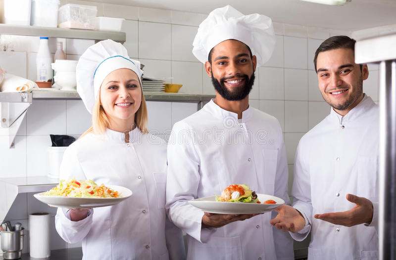 Chef and his assistants preparing meal. Smiling chef and his assistants preparing meal indoors royalty free stock image
