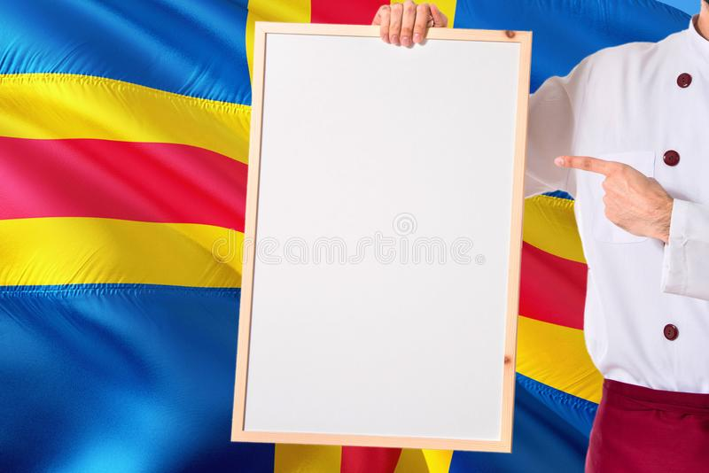 Chef holding blank whiteboard menu on Aland Islands flag background. Cook wearing uniform pointing space for text.  stock photography