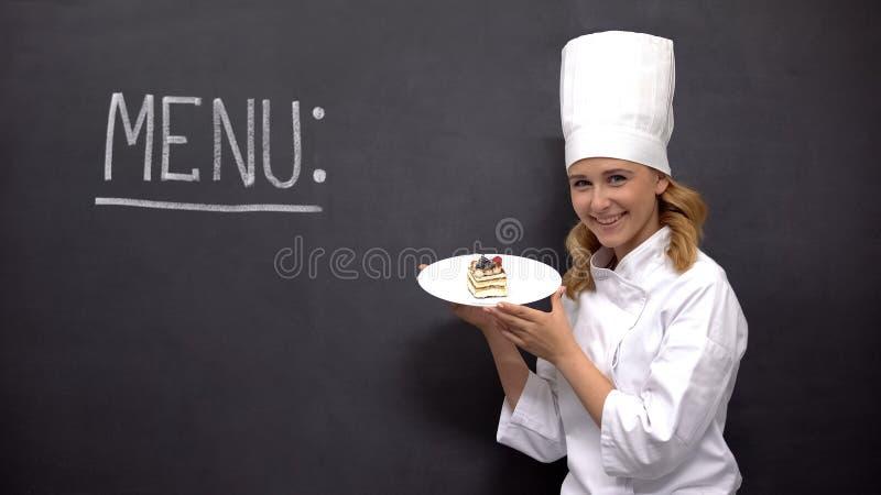 Chef holding cake near Menu word on blackboard, offering desserts in restaurant royalty free stock photos