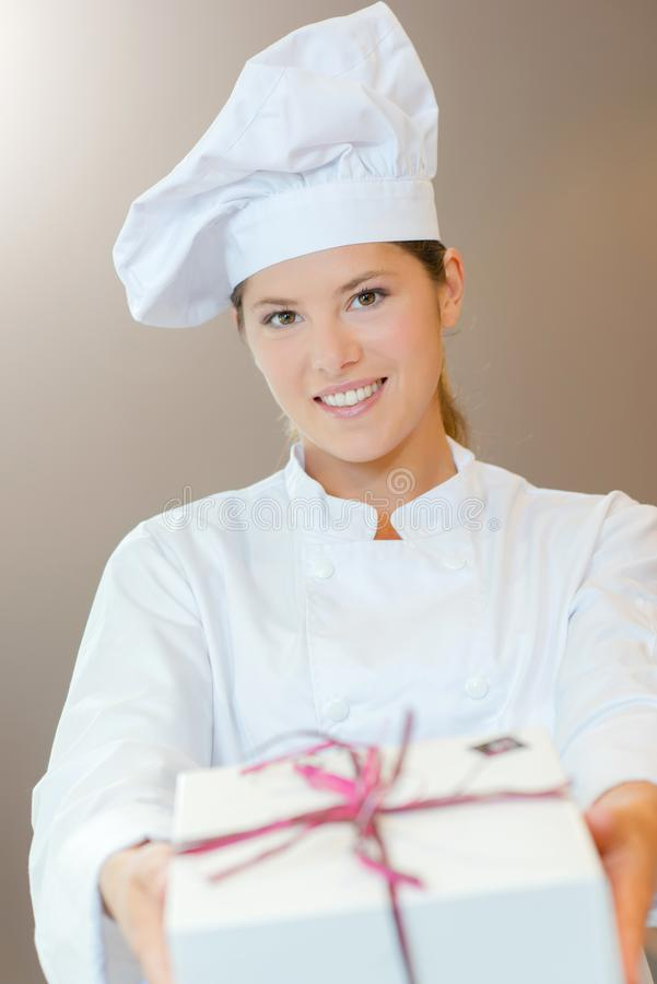 Chef holding forwards gift wrapped box. Chef holding forwards a gift wrapped box royalty free stock image