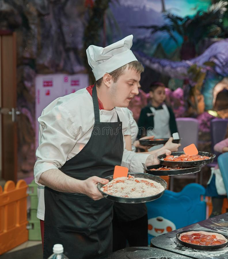 Chef is holding a freshly prepared pizza. Delicious food royalty free stock images