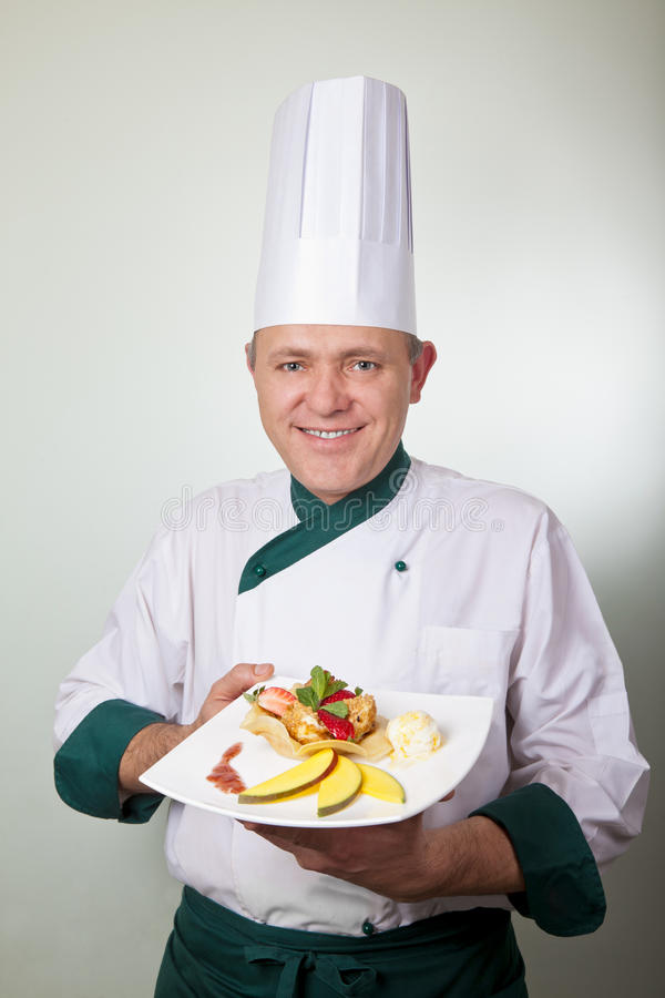 Chef holding fruit dessert royalty free stock photography