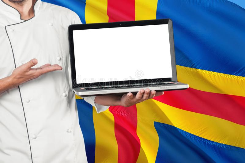 Chef holding laptop with blank screen on Aland Islands flag background. Cook wearing uniform and pointing laptop for copy space.  royalty free stock image