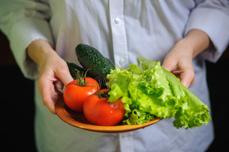 The chef is holding a plate with tomato cucumber and lettuce leaves royalty free stock photo
