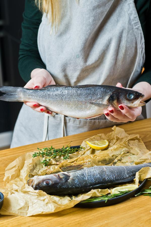 The chef is holding a sea bass. Black background, side view, space for text. royalty free stock photography