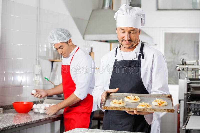 Chef Holding Small Pizzas sur Tray With Colleague photographie stock libre de droits