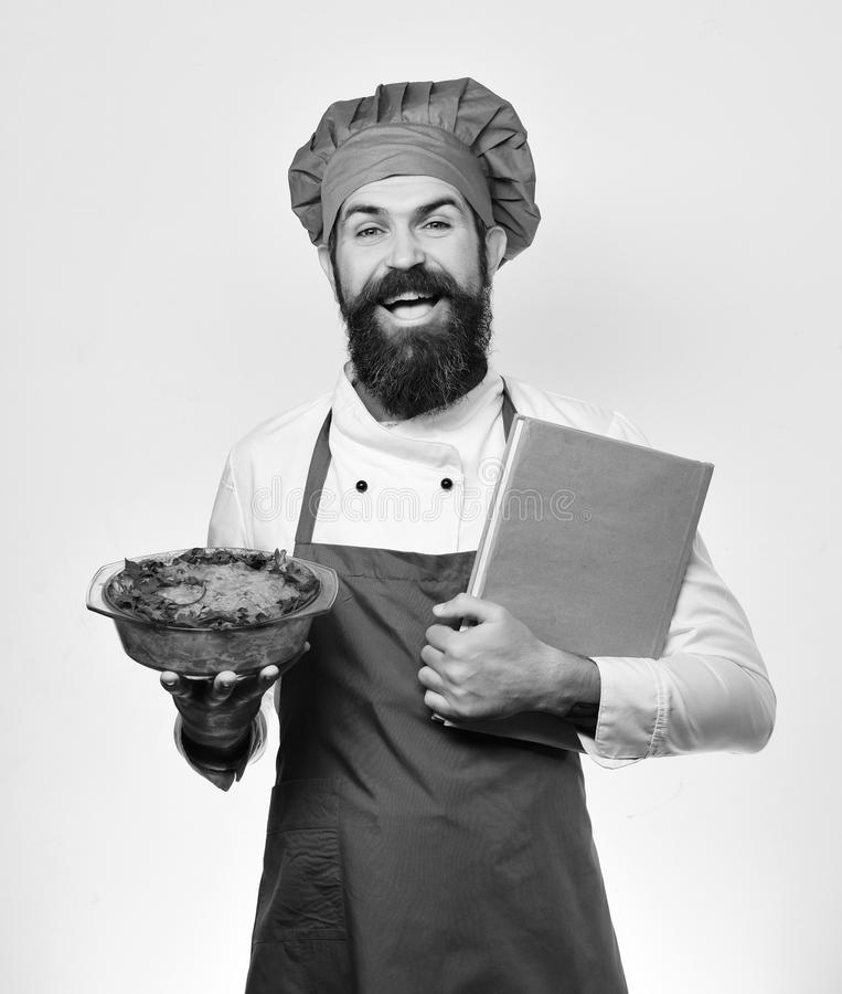 Chef holds bowl with potato casserole and price list. Order and cooking service concept. Man with beard isolated on white background. Cook with happy face in stock photo