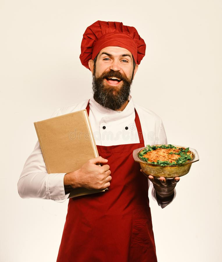 Chef holds bowl with potato casserole and price list. Order and cooking service concept. Man with beard isolated on white background. Cook with happy face in royalty free stock image