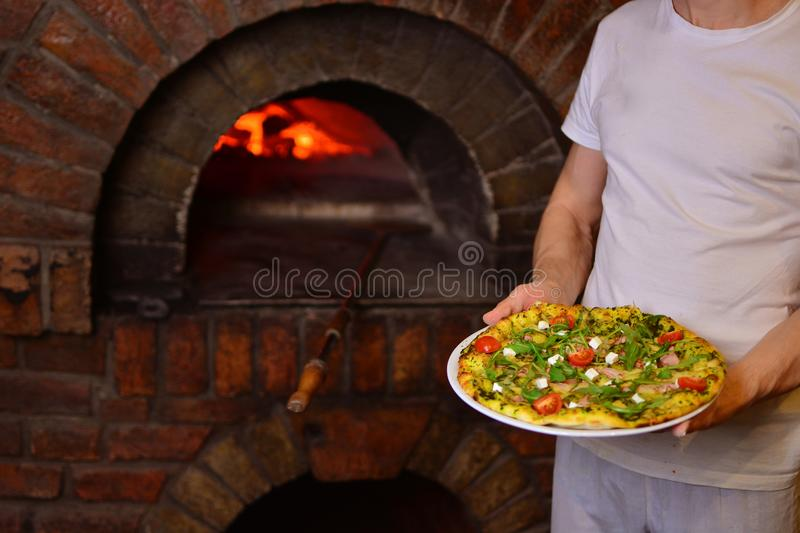 Chef holds a tasty pizza in his hands royalty free stock images