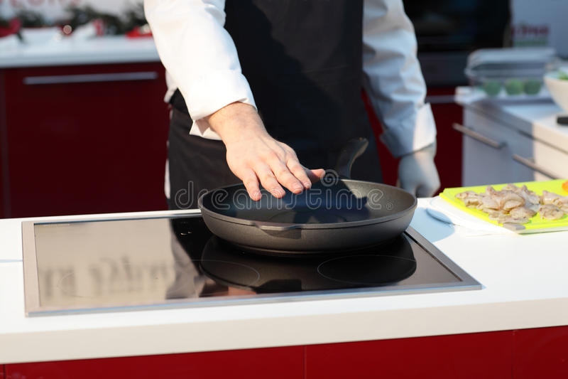 Chef and hot pan. Chef holds his hand over a hot pan at kitchen stock images