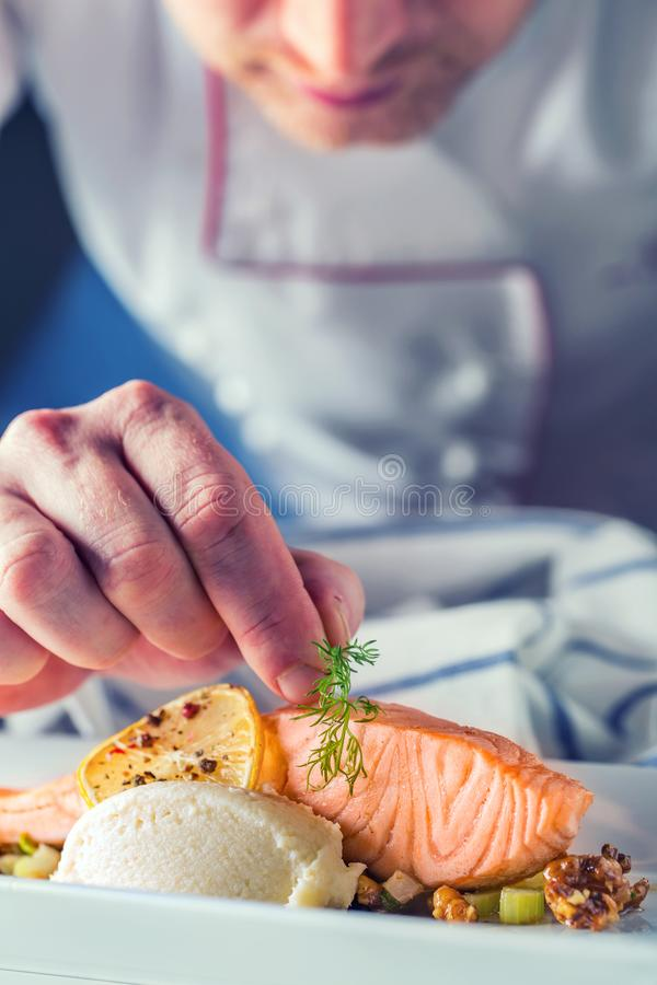 Chef in hotel or restaurant kitchen cooking, only hands. Prepared salmon steak with dill decoration stock photography