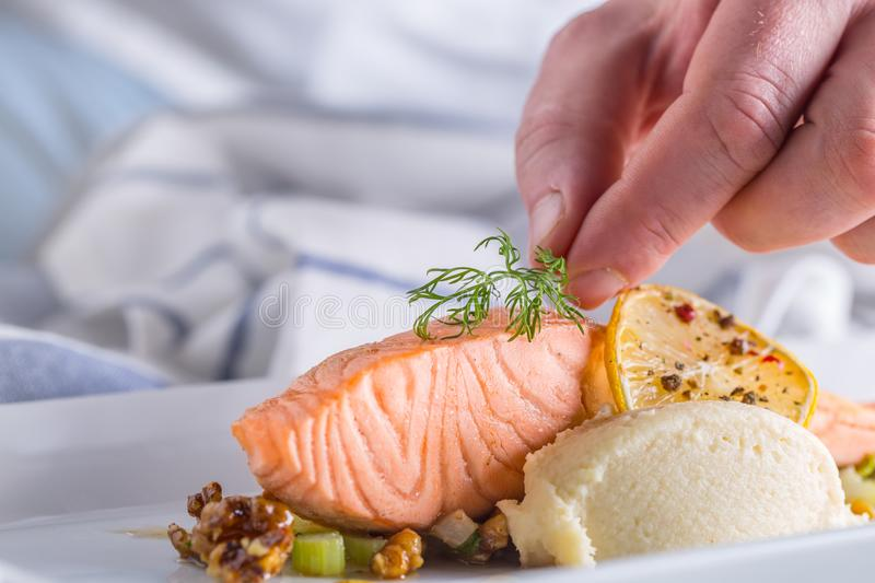 Chef in hotel or restaurant kitchen cooking, only hands. Prepared salmon steak with dill decoration.  royalty free stock image