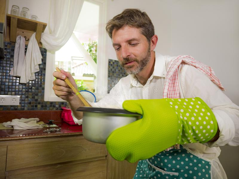 Domestic lifestyle portrait of happy and attractive  man in kitchen apron and glove holding cooking pot excited with delicious royalty free stock photos