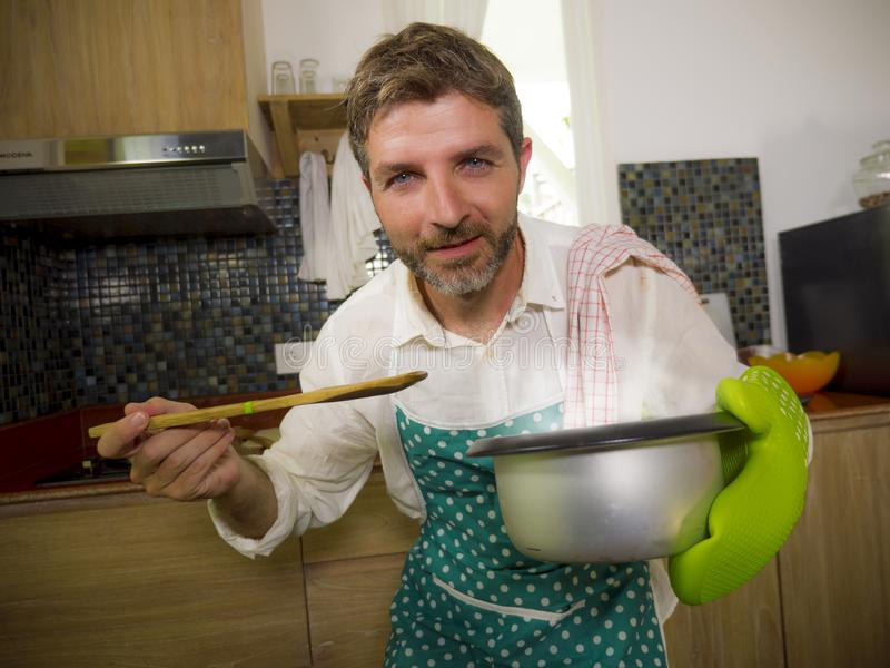 Domestic lifestyle portrait of happy and attractive  man in kitchen apron and glove holding cooking pot excited with delicious stock photo