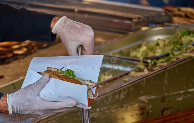 Chef with hygienic rubber gloves and a pair of tongs prepares a fish roll from a roll, a piece of mackerel fillet and a salad with. Onions royalty free stock image