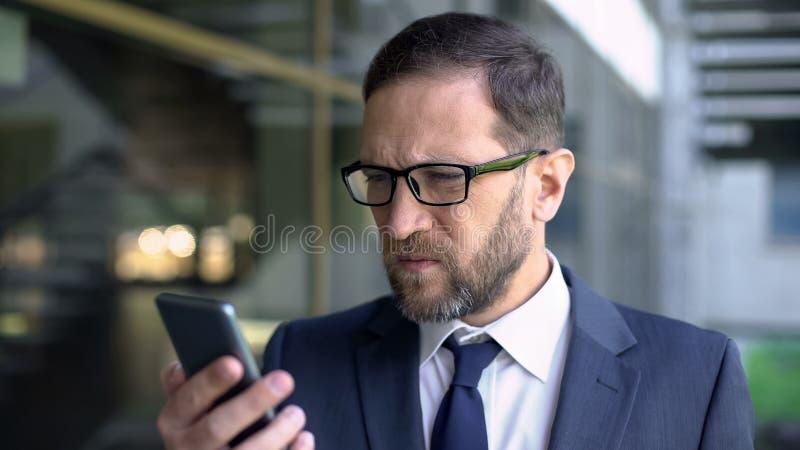 Chef i glasögon som försöker det lästa smartphonemeddelandet, fattig synförmåga, hälsovård royaltyfria foton