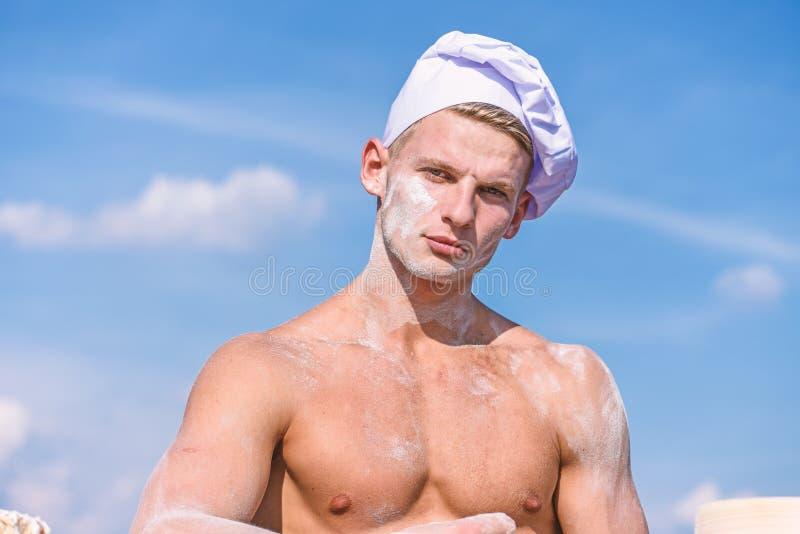 Chef im weißen Hut auf strengem Gesicht, Himmel auf Hintergrund Mann mit attraktiver Erscheinung arbeitet als Koch oder Bäcker, K stockfotos