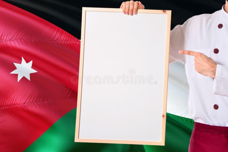 Chef jordanien tenant le menu vide de tableau blanc sur le fond de drapeau de la Jordanie Faites cuire l'uniforme de port dirigea photo libre de droits