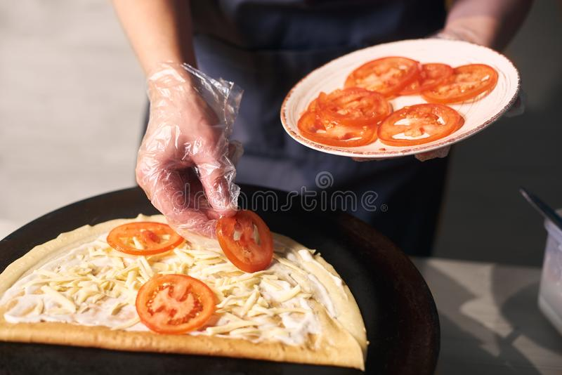 Chef keeping plate with cutted tomato. Woman hand putting tomato slices on pancake lubricated with sauce. Front view. stock photos