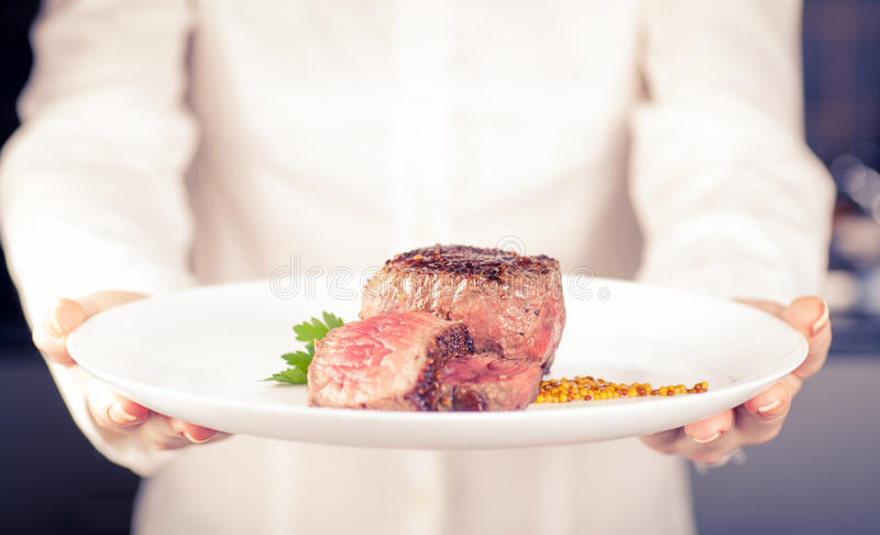 Chef keeps a dish. Of medallions in hands stock images