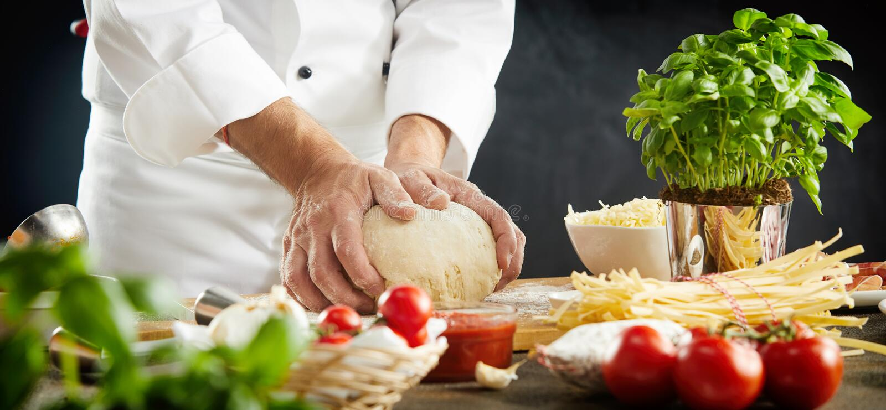 Chef kneading raw dough for an Italian pizza royalty free stock photos