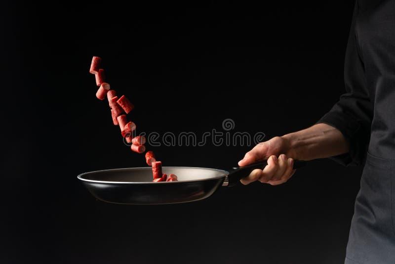 Chef kocht Pepperoniw?rste, auf einem schwarzen Hintergrund, ein Rezeptbuch, deutsche W?rste, Bierimbisse stockbilder
