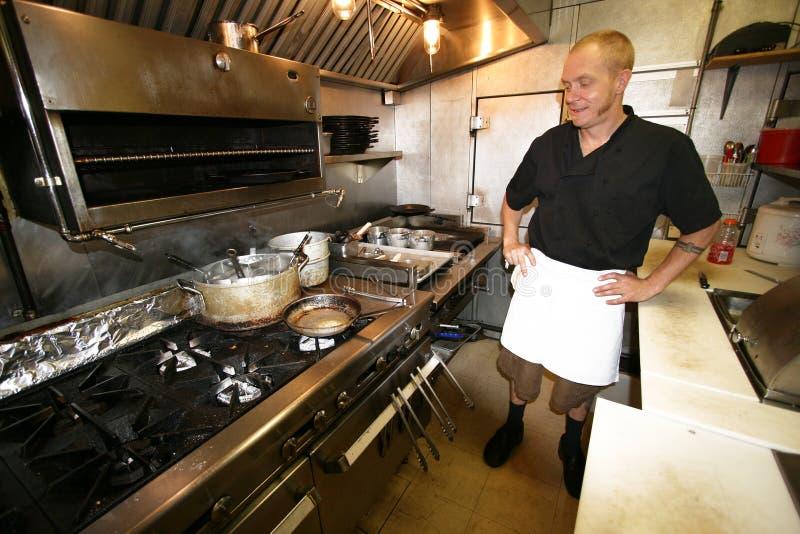 Chef-kok aan het werk in kleine keuken royalty-vrije stock afbeelding
