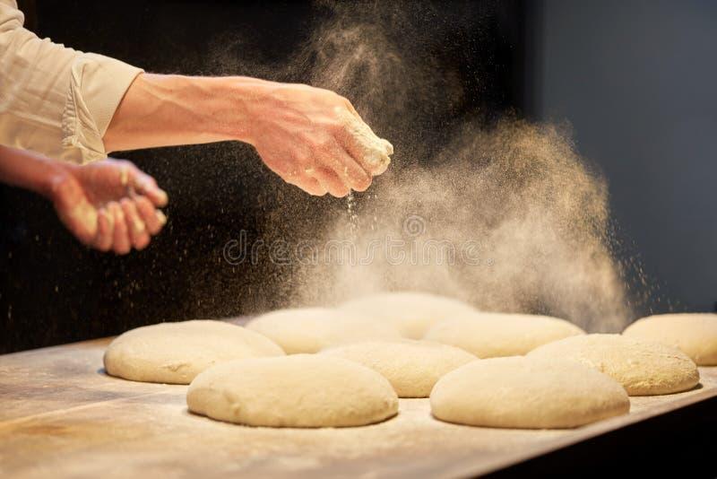 Chef-kok of bakkers kokend deeg bij bakkerij royalty-vrije stock fotografie