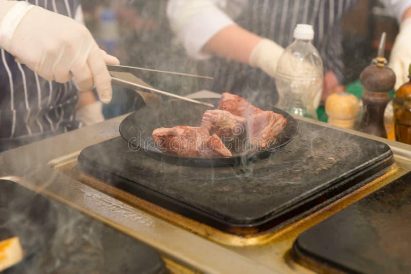 Chef-kok bradend vlees in een wok over een rooster royalty-vrije stock afbeeldingen