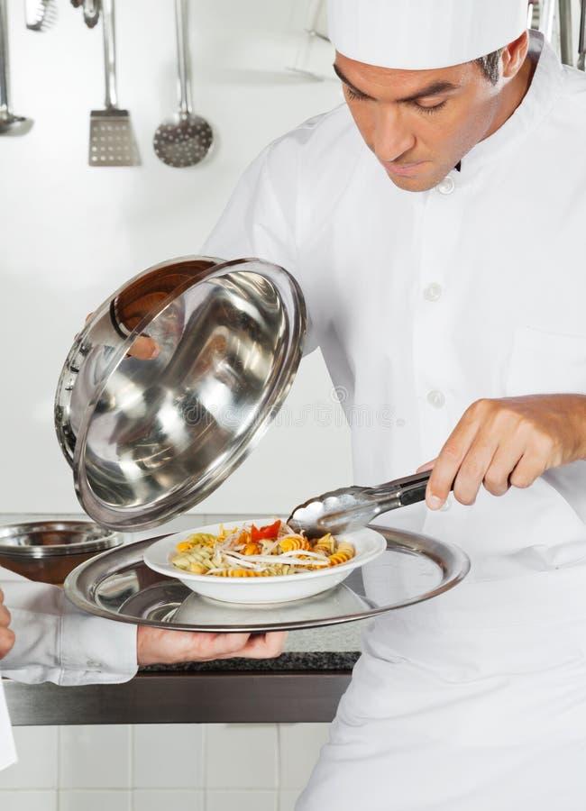 Chef-kok Checking Pasta Dish met Tong royalty-vrije stock foto