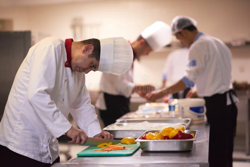 Chef-kok in de plakgroenten van de hotelkeuken met mes stock afbeelding