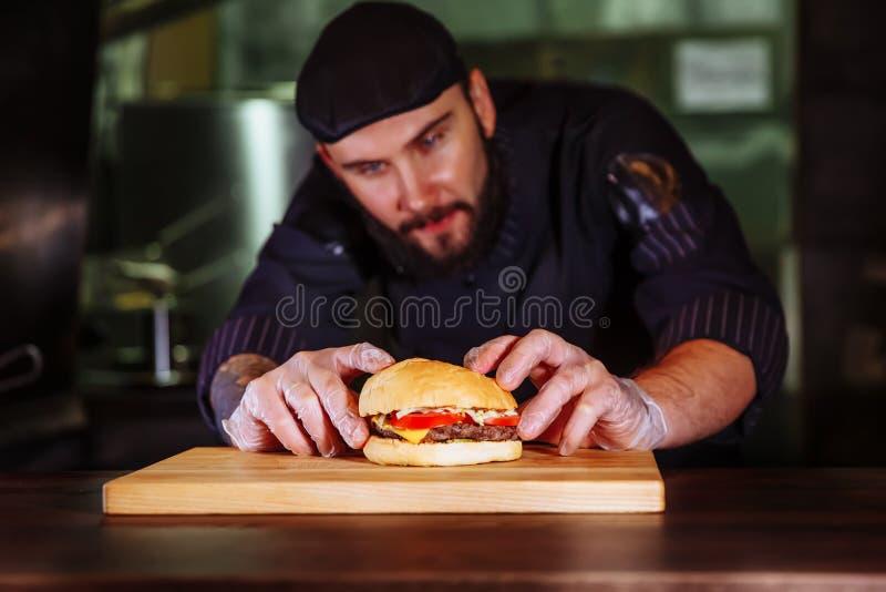 Chef-kok die broodje op bovenkant zetten, hij die een rundvleeshamburger voor klantenorde maken stock foto