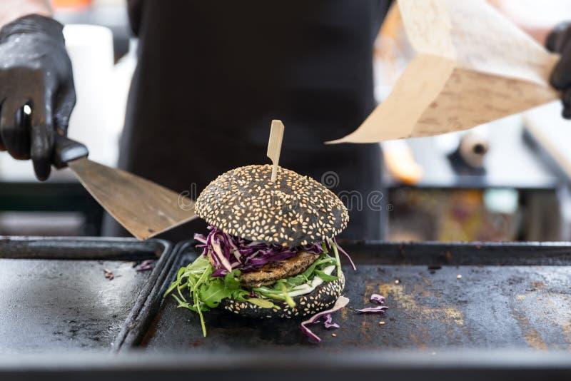 Chef-kok die burgers voorbereiden bij grillplaat op het internationale stedelijke festival van het straatvoedsel royalty-vrije stock fotografie