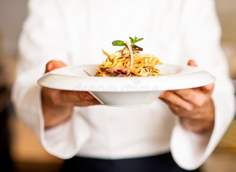 Chef-kok die deegwarensalade aanbieden aan u royalty-vrije stock fotografie