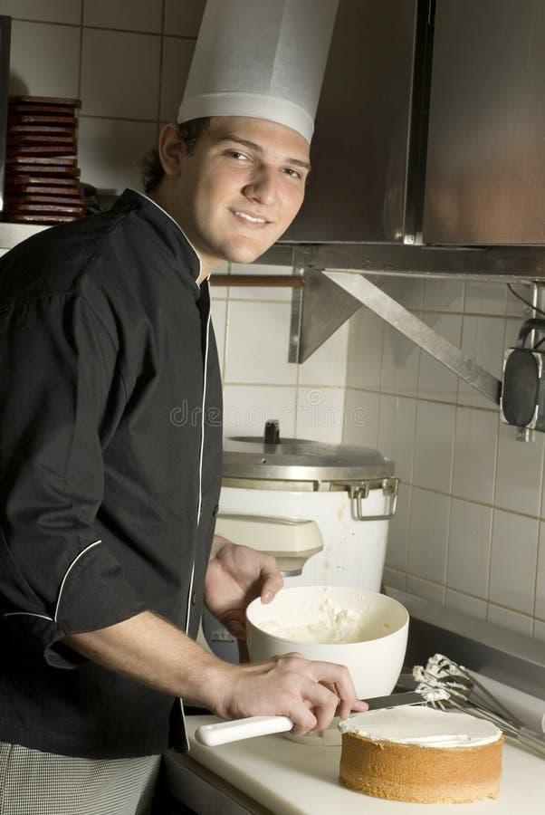 Chef-kok die een Cake bevriest stock afbeelding